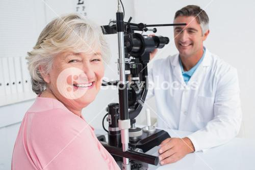 Senior woman smiling while sitting with optician