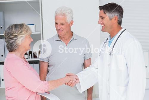 Senior couple smiling while visiting doctor