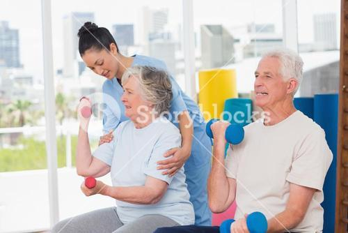 Instructor assisting senior woman in lifting dumbbells by man
