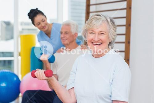 Senior woman lifting dumbbells while sitting with man and instructor