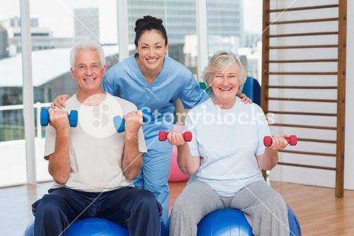 Happy female instructor with arms around senior couple