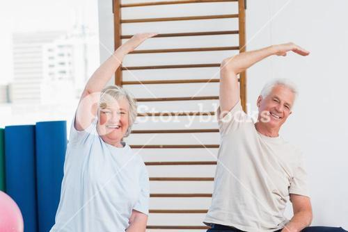 Senior couple doing stretching exercise in fitness studio