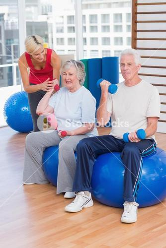 Trainer motivating senior couple in lifting dumbbells