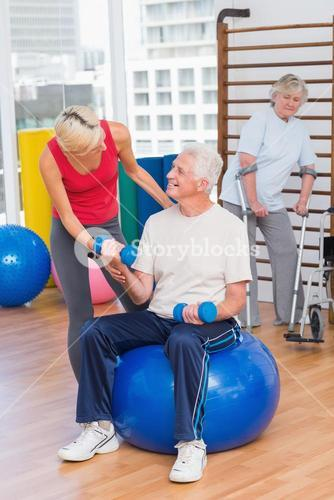 Trainer assisting senior man in lifting dumbbells