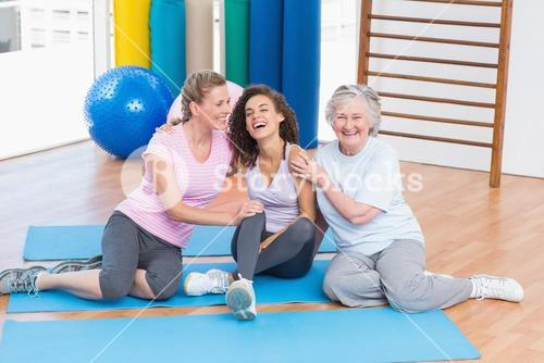 Playful friends sitting on exercise mat in gym