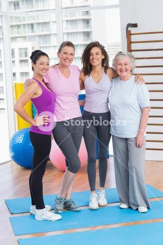 Portrait of happy women standing arms around