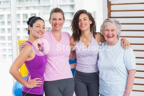 Happy women standing arms around in gym