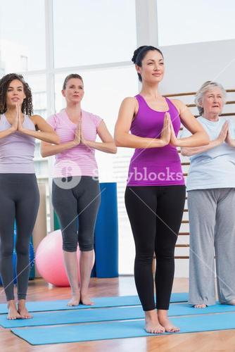 Female friends with hands clasped exercising in gym