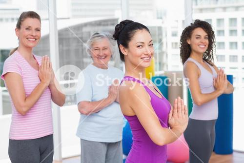 Friends with hands clasped standing in gym