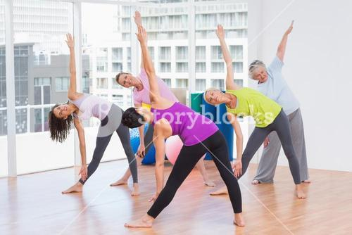 Instructor guiding friends in stretching exercise