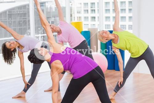 Female instructor guiding friends in stretching exercise