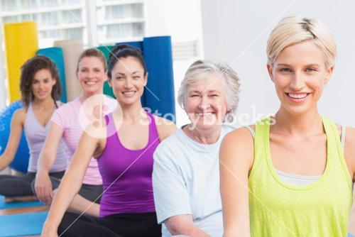 Women practicing yoga during fitness class