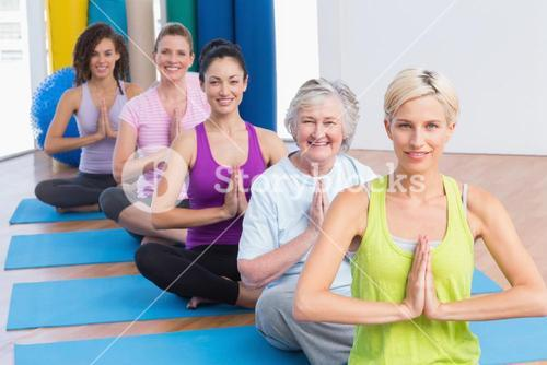 Women meditating with hands joined during fitness class