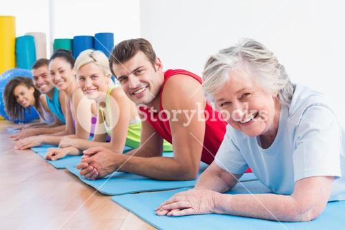 Senior woman with friends lying on exercise mats at gym