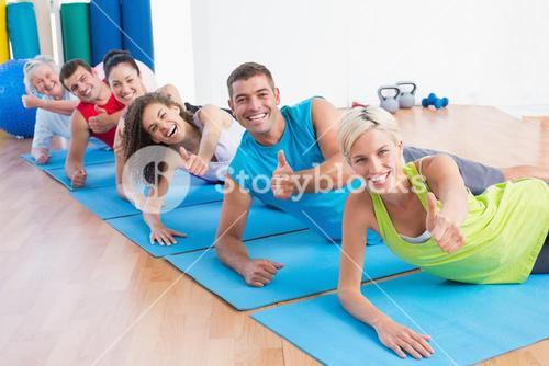 People on exercise mats gesturing thumbs up at gym