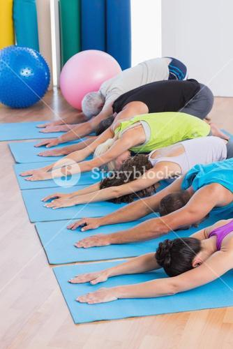 People practicing child pose in gym