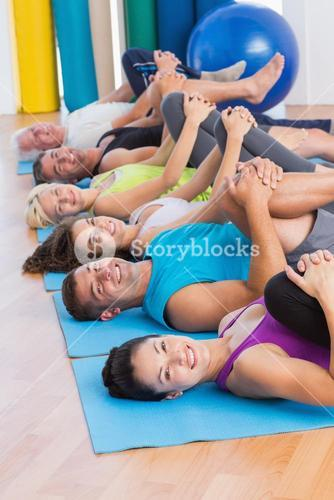 People stretching legs in yoga class