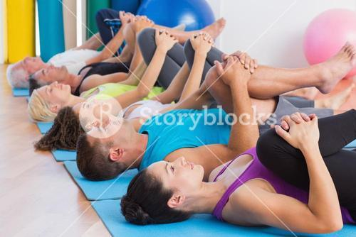 People stretching legs on exercise mats at gym