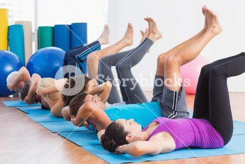 People practicing yoga on exercise mats at fitness studio