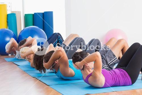 People doing sit-ups on exercise mats
