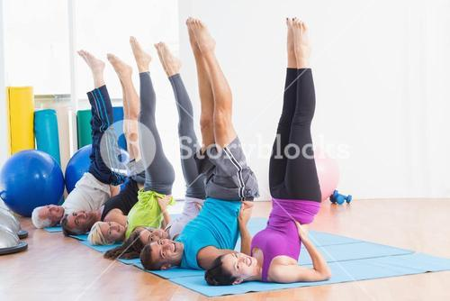 People doing Pilates exercises in gym