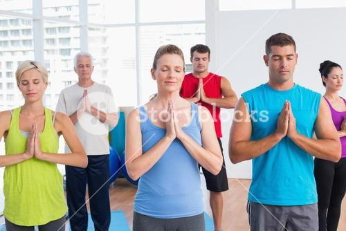 People meditating with hands joined in fitness club
