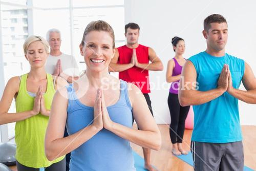 People meditating with hands joined in yoga class