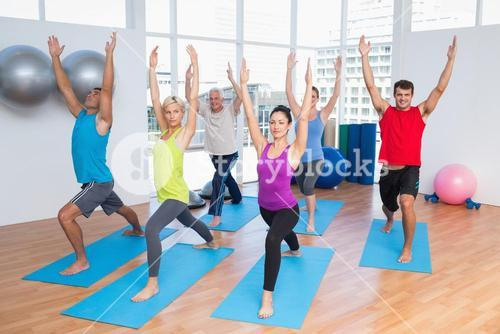 People with hands raised doing yoga