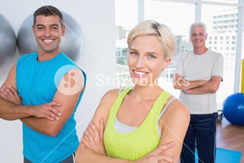 Happy friends standing arms crossed at gym class