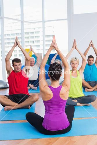 People practicing yoga in fitness club