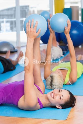 Woman exercising with medicine ball in fitness club