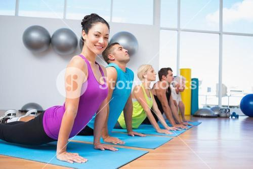 People doing the cobra pose in fitness studio