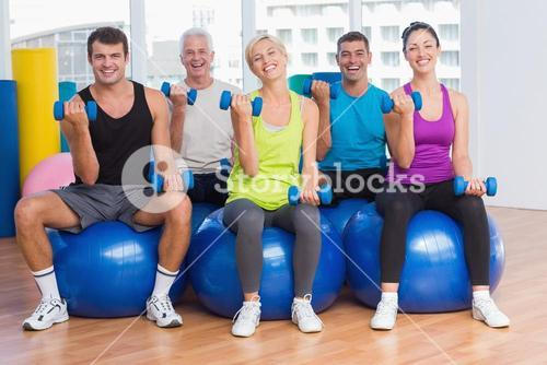 People working out on exercise balls at gym class