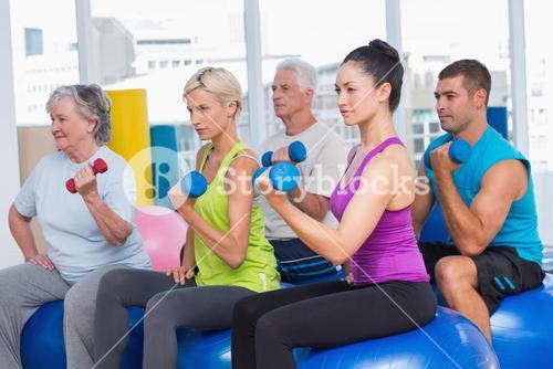 People working out with dumbbells in gym class