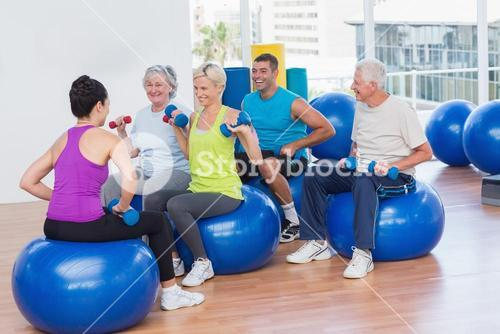 People lifting dumbbells in gym class