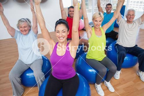 People sitting on exercise balls with hands raised