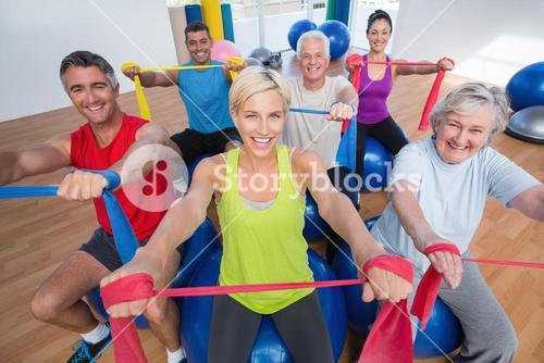 Happy people exercising with resistance bands in gym class