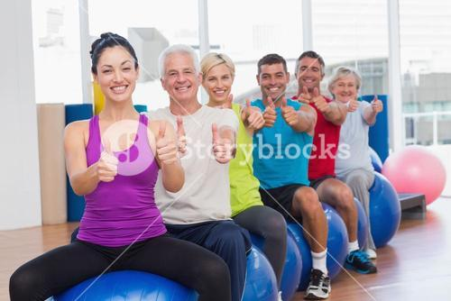 People sitting on exercising balls gesturing thumbs up