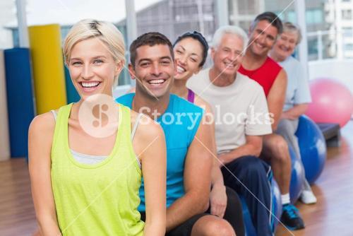 People relaxing on exercise balls in gym class