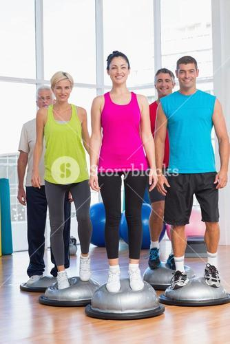 People standing on balance balls in gym