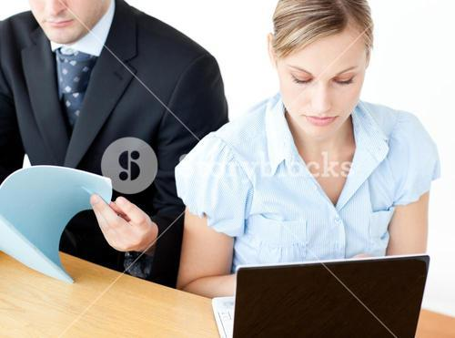 Couple of frustrated businesspeople reading a folder and using a laptop