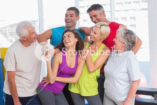 Playful friends looking at man at fitness studio