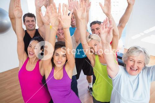 Cheerful friends with hands raised at fitness studio