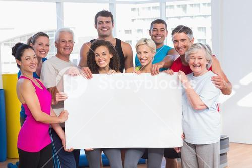 Happy people holding blank billboard at health club