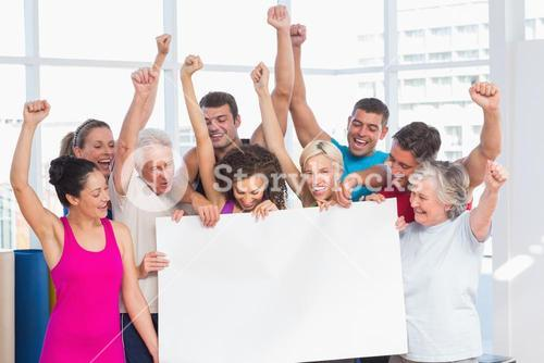Excited people holding blank billboard at gym