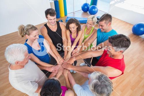 Fit people stacking hands at health club