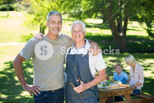 Happy man doing barbecue with his father