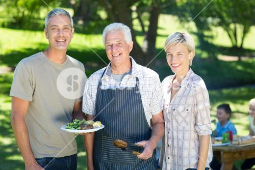 Happy couple with grandfather doing barbecue
