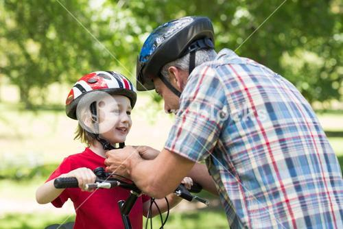 Father attaching his sons cycling helmet