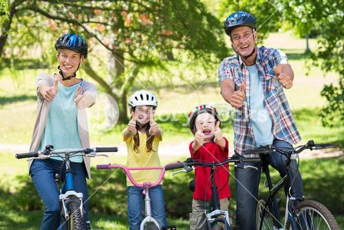 Happy family on their bike with thumbs up at the park